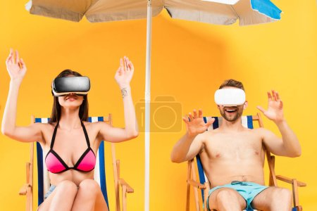 Photo for Smiling couple in virtual reality headsets sitting on deck chairs and gesturing near beach umbrella on yellow - Royalty Free Image