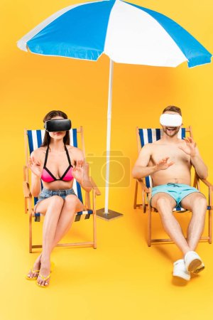 Photo for Happy couple in virtual reality headsets sitting on deck chairs and gesturing near beach umbrella on yellow - Royalty Free Image