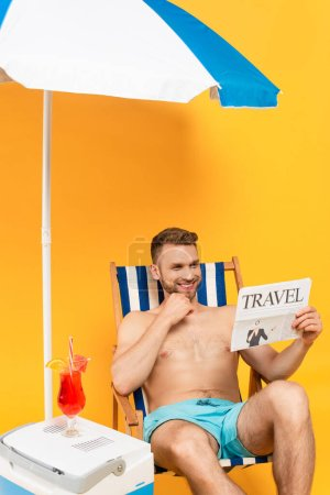 Photo for Shirtless man smiling while reading travel newspaper and sitting on deck chair near cocktail on portable fridge freezer on yellow - Royalty Free Image