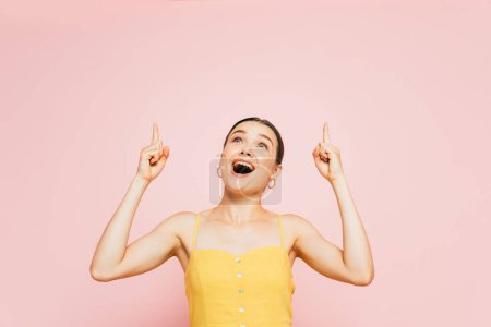 Photo pour Excité brunette jeune femme pointant avec les doigts vers le haut isolé sur rose - image libre de droit
