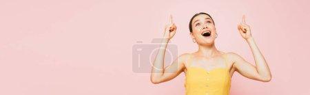 Photo pour Excité brunette jeune femme pointant avec les doigts vers le haut isolé sur rose, panoramique shot - image libre de droit