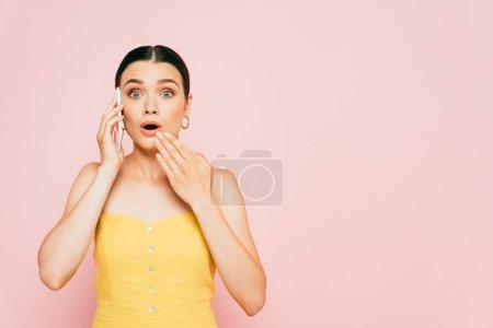 Photo pour Choqué brunette jeune femme parler sur smartphone isolé sur rose - image libre de droit