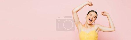 Photo pour Excitée jeune femme brune dans les écouteurs dansant isolé sur rose, plan panoramique - image libre de droit