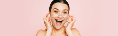 Photo for Excited brunette young woman listening music in earphones isolated on pink, panoramic shot - Royalty Free Image