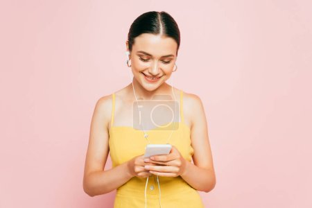 brunette young woman listening music in earphones and holding smartphone isolated on pink