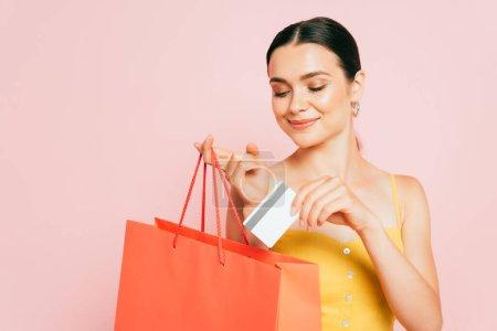 Photo pour Brunette jeune femme mettre carte de crédit dans un sac isolé sur rose - image libre de droit