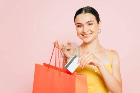 Foto de Morena joven poniendo tarjeta de crédito en bolsa aislada en rosa - Imagen libre de derechos