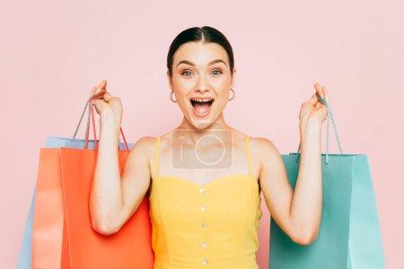 Photo pour Excitée jeune femme brune avec des sacs à provisions isolés sur rose - image libre de droit