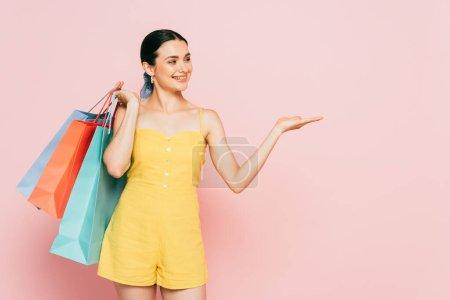 Foto de Morena joven con bolsas de compras apuntando con la mano a un lado en rosa - Imagen libre de derechos