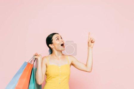 Photo pour Jeune femme brune choquée avec des sacs à provisions pointant vers le haut sur rose - image libre de droit