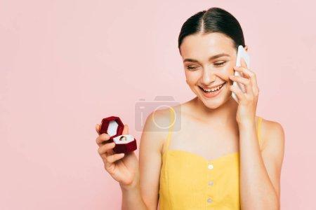 Photo pour Brunette jeune femme tenant boîte avec bague de fiançailles tout en parlant sur smartphone isolé sur rose - image libre de droit