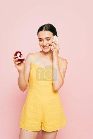 Photo pour Brunette jeune femme tenant boîte avec bague de fiançailles tout en parlant sur smartphone sur rose - image libre de droit