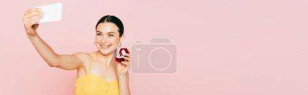 selektiver Fokus der brünetten jungen Frau, die eine Schachtel mit Verlobungsring hält, während sie ein Selfie isoliert auf einer rosa, panoramischen Aufnahme macht
