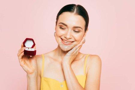 Photo pour Brunette jeune femme tenant boîte avec bague de fiançailles isolée sur rose - image libre de droit