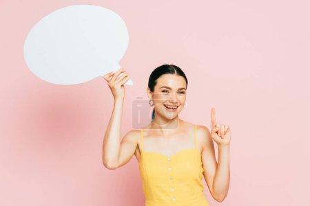 brunette young woman with white blank speech bubble showing idea gesture on pink