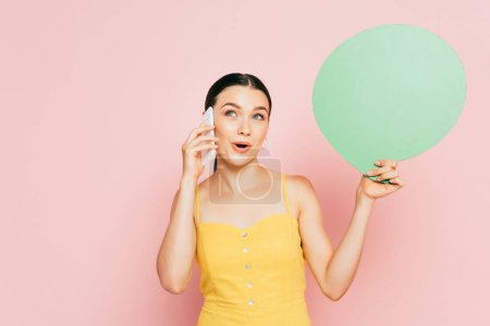 surprised brunette young woman with green blank speech bubble talking on smartphone on pink