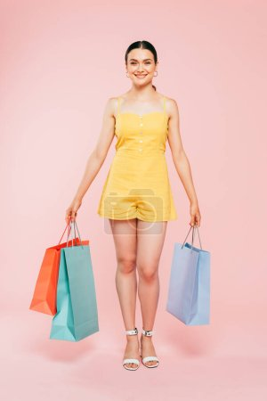 Photo for Full length view of brunette young woman with shopping bags on pink - Royalty Free Image