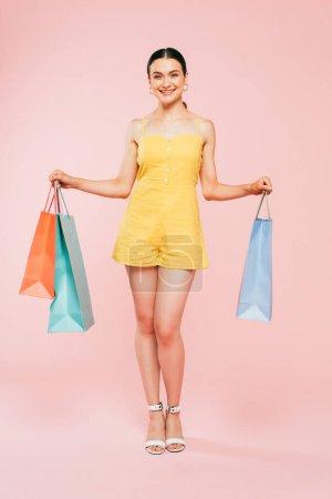 Photo pour Vue pleine longueur de brune jeune femme avec des sacs à provisions sur rose - image libre de droit