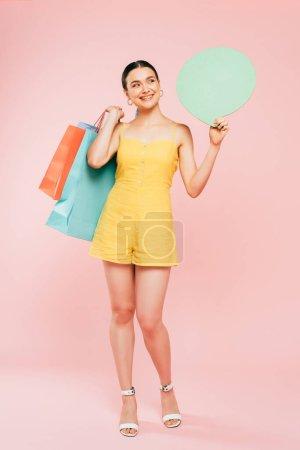 Foto de Vista completa de la mujer joven morena con bolsas de compras y burbuja del habla en rosa - Imagen libre de derechos