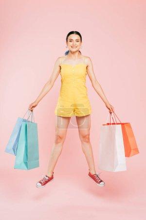 Photo pour Vue pleine longueur de brune jeune femme sautant avec des sacs à provisions sur rose - image libre de droit
