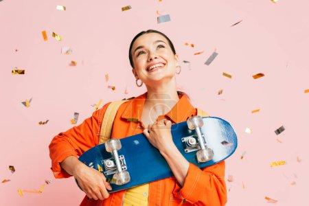 Photo pour Brunette jeune femme en tenue colorée avec planche à roulettes sous confettis tombant isolé sur rose - image libre de droit