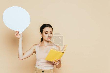 Foto de Morena joven con el discurso en blanco burbuja lectura libro en beige - Imagen libre de derechos