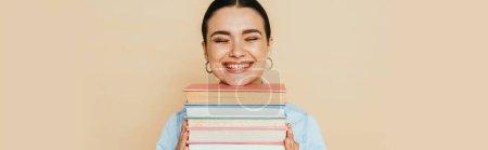 Photo pour Étudiant en chemise denim avec des livres souriant isolé sur beige, vue panoramique - image libre de droit