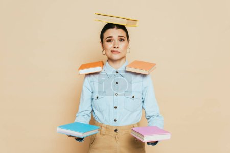 skeptical student in denim shirt with books on body isolated on beige