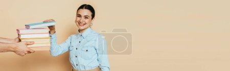 Photo pour Étudiant en chemise denim prenant des livres sur beige, panoramique - image libre de droit