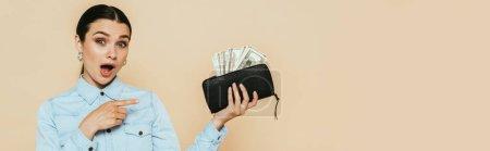 Photo pour Femme brune choquée en chemise denim pointant vers portefeuille avec des dollars isolés sur beige, vue panoramique - image libre de droit