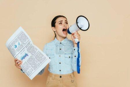 femme brune en chemise denim avec journal criant dans haut-parleur isolé sur beige
