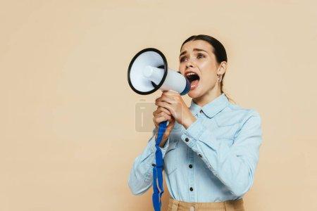 brunette woman in denim shirt screaming in loudspeaker isolated on beige