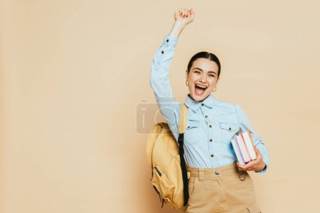 Photo for Excited brunette student in denim shirt with books and backpack on beige - Royalty Free Image