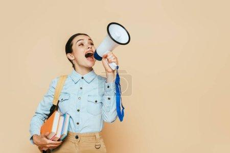 Photo pour Vue latérale d'une étudiante brune en chemise denim avec livres et sac à dos criant en haut-parleur sur beige - image libre de droit