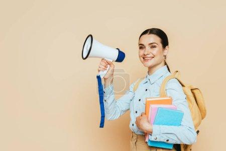 Photo pour Vue latérale de l'étudiante brune en chemise denim avec livres et sac à dos tenant haut-parleur sur beige - image libre de droit