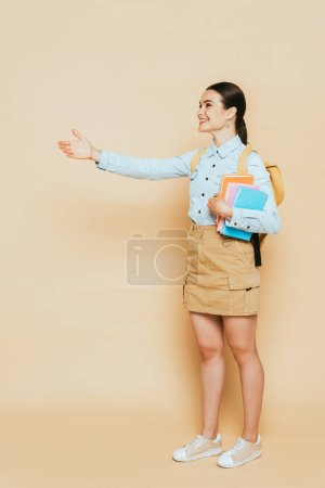 full length view of brunette student in denim shirt with books and backpack outstretching hand on beige
