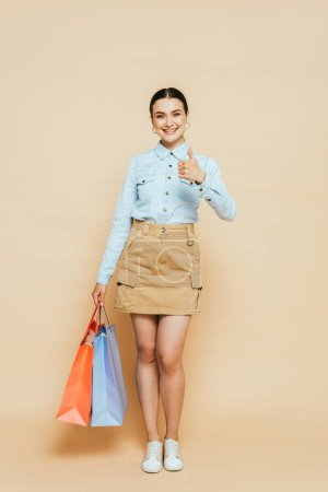 Photo for Full length view of brunette woman in denim shirt with shopping bags showing thumb up on beige - Royalty Free Image