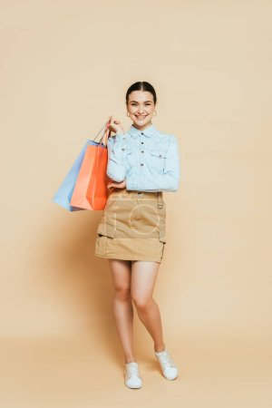Photo for Full length view of brunette woman in denim shirt with shopping bags on beige - Royalty Free Image