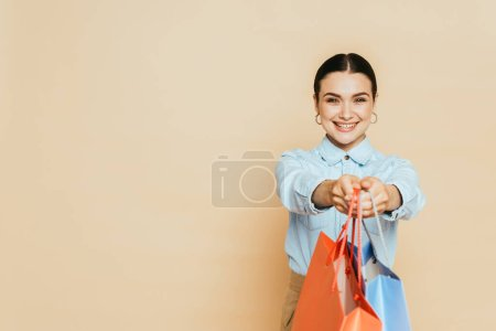 Photo for Brunette woman in denim shirt giving shopping bags on beige - Royalty Free Image