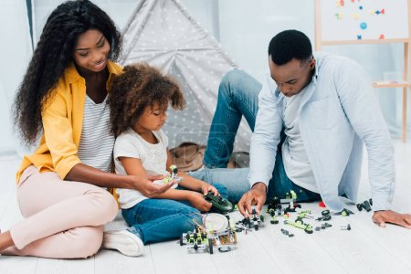 african american parents sitting on floor with daughter near plastic toys