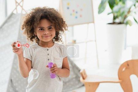 Photo pour Frisé afro-américain gamin regardant caméra près brillant bulle de savon - image libre de droit