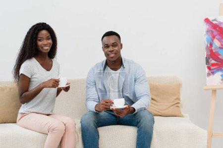 couple afro-américain tenant des tasses avec café et assis sur le canapé