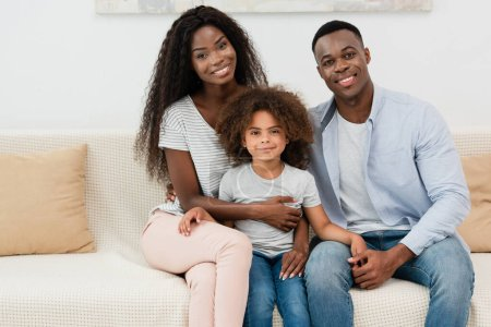 Photo pour Afro-américaine famille regardant caméra et assis sur canapé dans le salon - image libre de droit