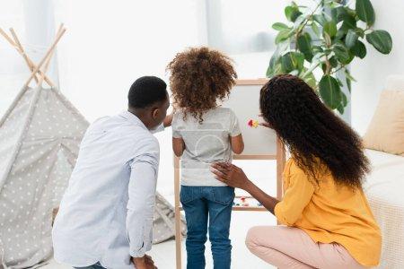 vista posterior de la familia afroamericana cerca del caballete magnético