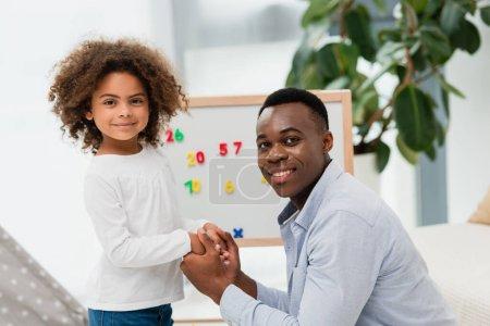 afrikanisch-amerikanischer Vater und Tochter beim Händchenhalten zu Hause