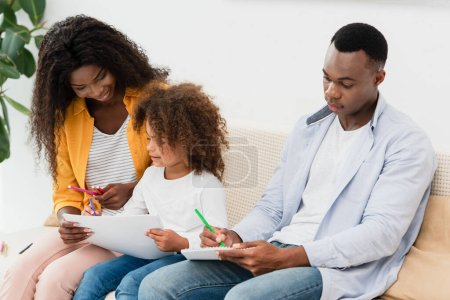 Photo pour Dessin de famille afro-américaine avec crayons de couleur assis sur le canapé - image libre de droit