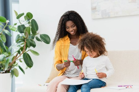 Photo for African american mother holding color pencil while sitting on sofa with curly daughter - Royalty Free Image