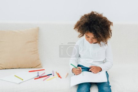 curly african american kid sitting on sofa and drawing with color pencil