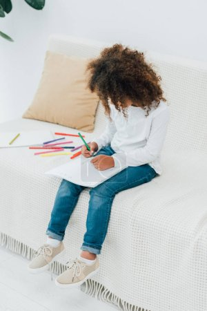 Photo for Curly african american kid drawing with color pencil while sitting on sofa - Royalty Free Image