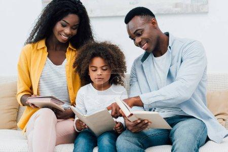 Photo pour Parents afro-américains et enfant regardant le livre - image libre de droit
